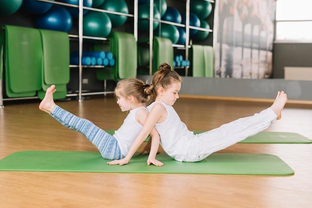 Zijaanzicht van twee klein meisjeskind dat yogaoefeningen doet Gratis Foto