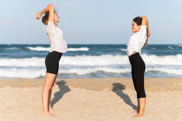 Zijaanzicht van twee vrouwelijke vrienden die op het strand uitoefenen Gratis Foto