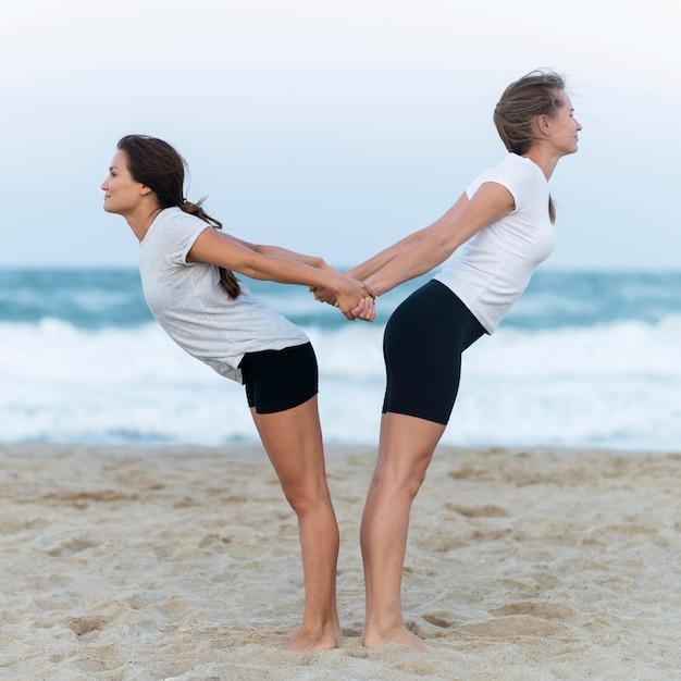 Zijaanzicht van twee vrouwen die zich uitstrekt op het strand Gratis Foto