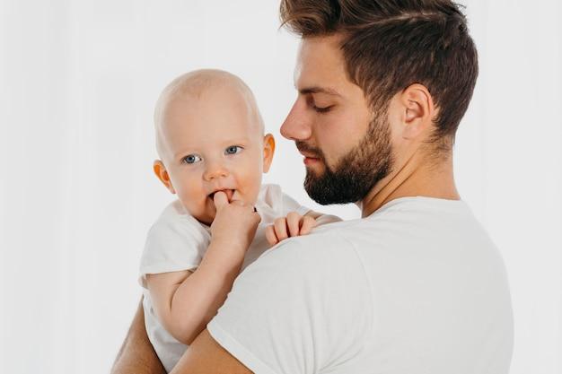 Zijaanzicht van vader die zijn baby houdt Gratis Foto