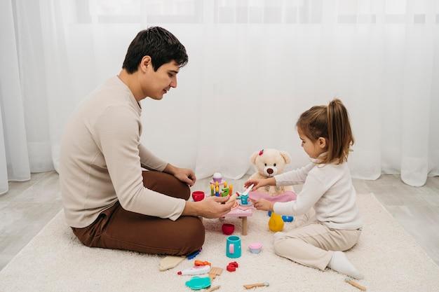 Zijaanzicht van vader en dochter samen thuis Gratis Foto