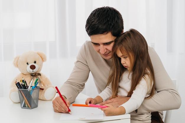 Zijaanzicht van vader en dochter thuis samen Gratis Foto