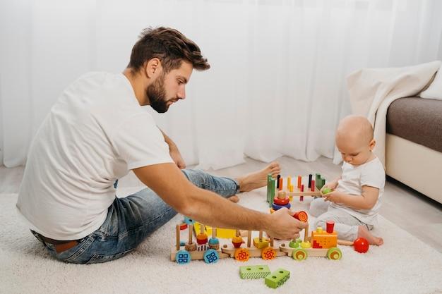 Zijaanzicht van vader spelen met zijn baby Gratis Foto
