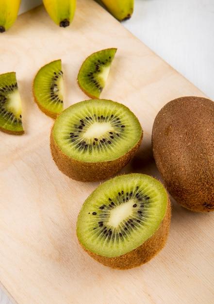 Zijaanzicht van vers kiwifruit en plakken van kiwi op een houten scherpe raad op wit Gratis Foto