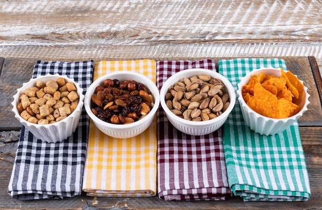 Zijaanzicht van verschillend soort snacks als noten, crackers en koekjes op servetten op witte houten horizontale oppervlakte Gratis Foto