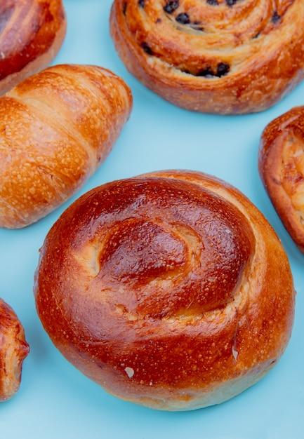 Zijaanzicht van verschillende bakkerijproducten als croissant brioche pijn aux rozijnen op blauwe ondergrond Gratis Foto
