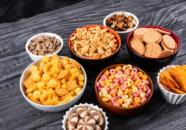 Zijaanzicht van verschillende soorten snacks als noten, crackers en koekjes in kommen op donkere horizontale oppervlakte Gratis Foto