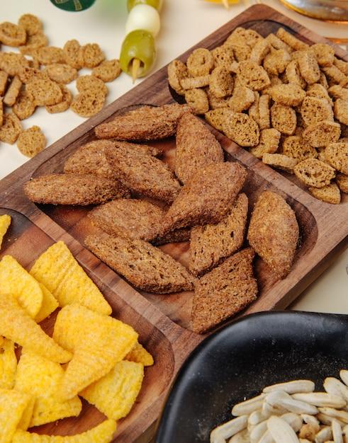 Zijaanzicht van verschillende zoute biersnacks broodcrackers graankegels op een houten schotel en zonnebloemenzaden en ingelegde olijven op wit Gratis Foto
