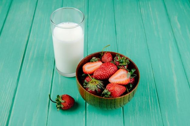 Zijaanzicht van verse rijpe aardbeien in een houten kom met een glas melk op groen hout Gratis Foto