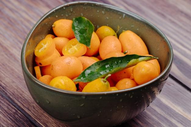 Zijaanzicht van verse rijpe kumquats met waterdalingen in een kom op rustiek hout Gratis Foto