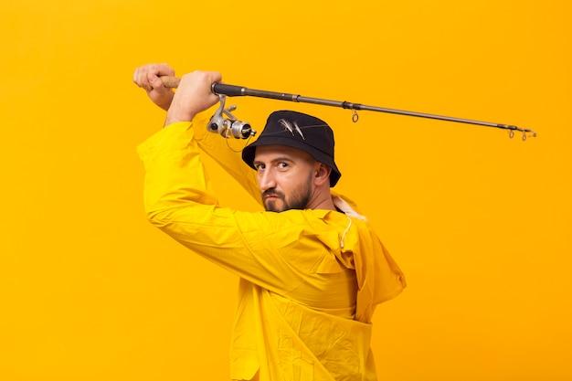 Zijaanzicht van visser die hengel steunt Gratis Foto