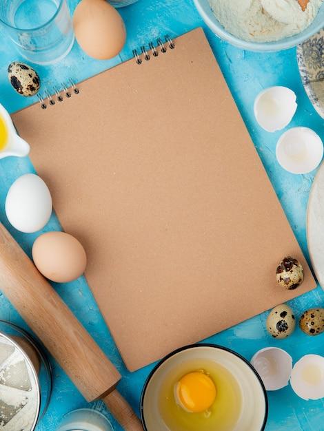 Zijaanzicht van voedsel als eigeel met water en deegrol op blauwe achtergrond met exemplaarruimte Gratis Foto