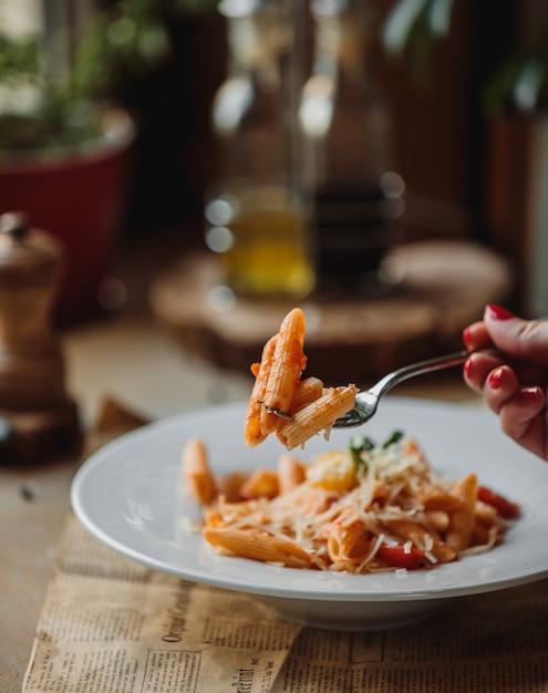Zijaanzicht van vork met pasta met tomatensaus en parmezaanse kaas Gratis Foto