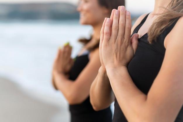 Zijaanzicht van vrienden die yoga op het strand doen Gratis Foto