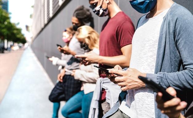 Zijaanzicht van vrienden met behulp van mobiele telefoon vallende gezichtsmasker Premium Foto
