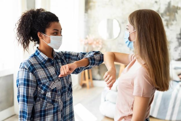 Zijaanzicht van vriendinnen met medische maskers die de elleboogbegroeting beoefenen Gratis Foto