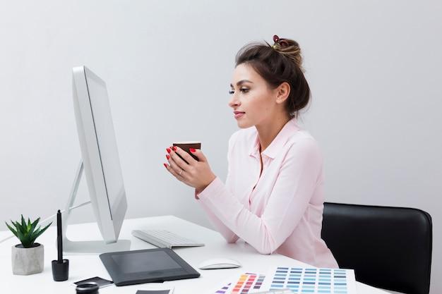 Zijaanzicht van vrouw die computer bekijkt terwijl het houden van kop van koffie Gratis Foto