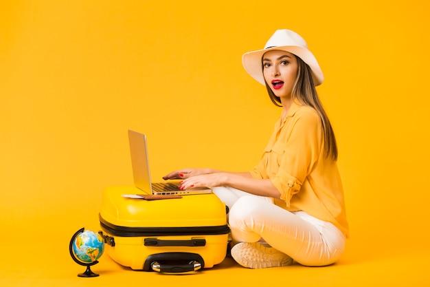 Zijaanzicht van vrouw die hoed draagt terwijl het werken aan laptop bovenop bagage Gratis Foto
