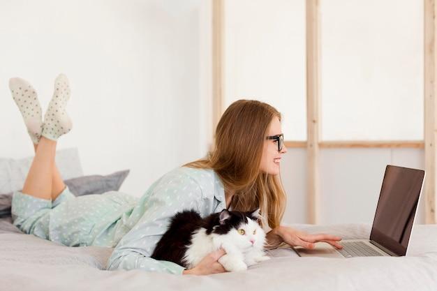 Zijaanzicht van vrouw die in pyjama van huis met kat werkt Gratis Foto