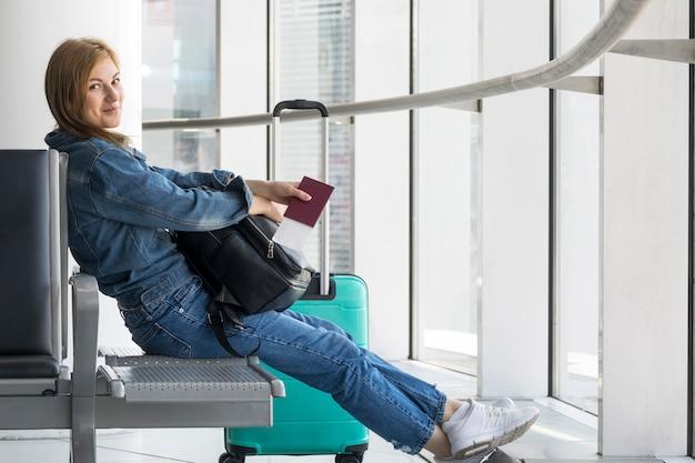 Zijaanzicht van vrouw die op vliegtuig wacht Gratis Foto
