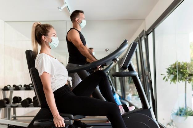 Zijaanzicht van vrouw en man in de sportschool met medische maskers Gratis Foto