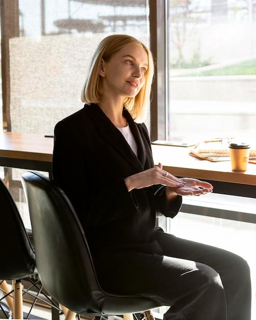Zijaanzicht van vrouw in café met gebarentaal Gratis Foto