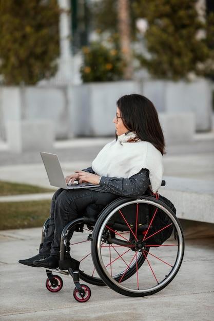 Zijaanzicht van vrouw in een rolstoel met laptop Gratis Foto