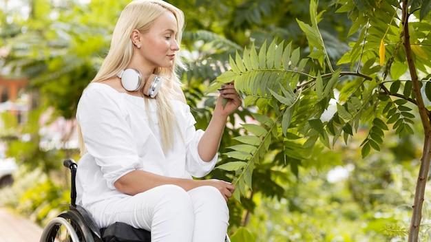 Zijaanzicht van vrouw in rolstoel buiten met plant Gratis Foto