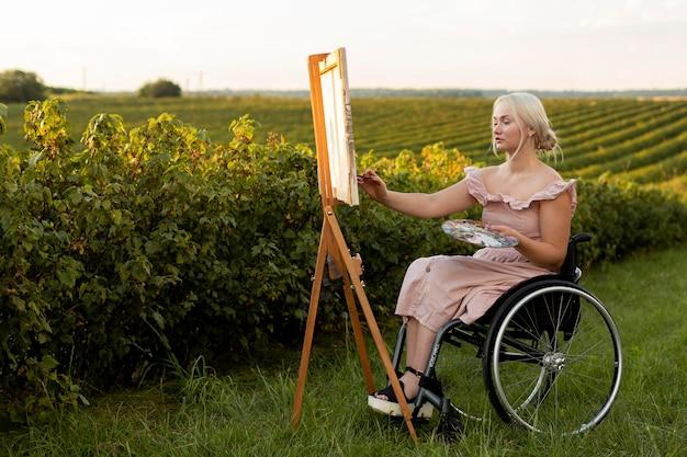 Zijaanzicht van vrouw in rolstoel buiten schilderen Premium Foto