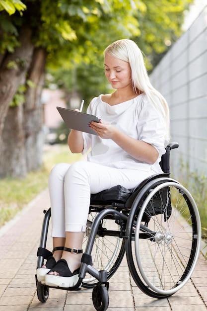 Zijaanzicht van vrouw in rolstoel met tablet Gratis Foto
