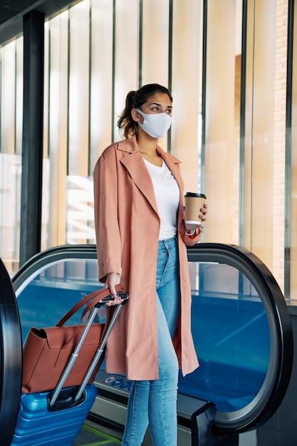 Zijaanzicht van vrouw met bagage en medisch masker tijdens de pandemie op de luchthaven Gratis Foto