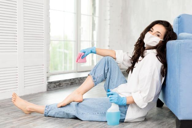 Zijaanzicht van vrouw met gezichtsmasker die terwijl het schoonmaken stellen Premium Foto