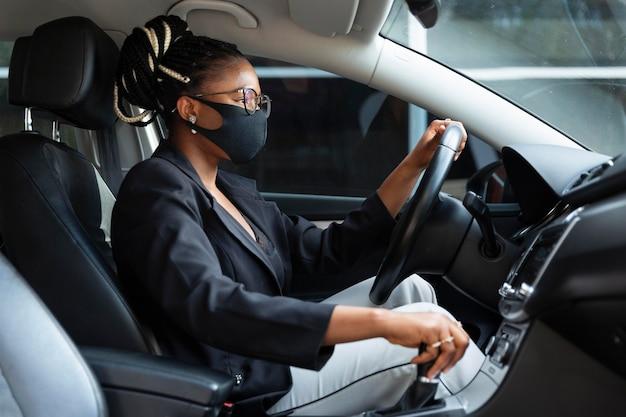 Zijaanzicht van vrouw met gezichtsmasker rijdende auto Premium Foto