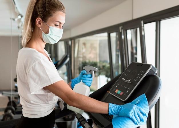 Zijaanzicht van vrouw met handschoenen en reinigingsoplossing fitnessapparatuur desinfecteren Gratis Foto