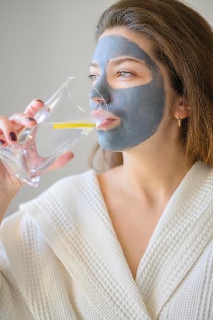 Zijaanzicht van vrouw met het drinkwater van het gezichtsmasker met citroen Gratis Foto