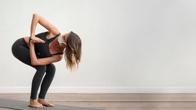 Zijaanzicht van vrouw met medisch masker die yoga met exemplaarruimte doet Gratis Foto