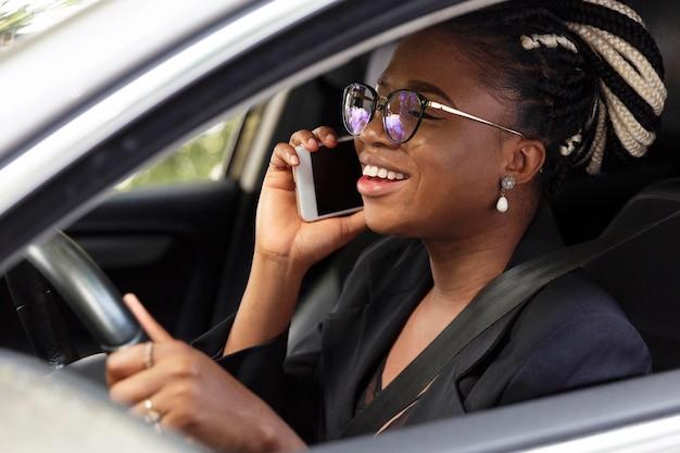 Zijaanzicht van vrouw privé auto rijden en praten over smartphone Gratis Foto