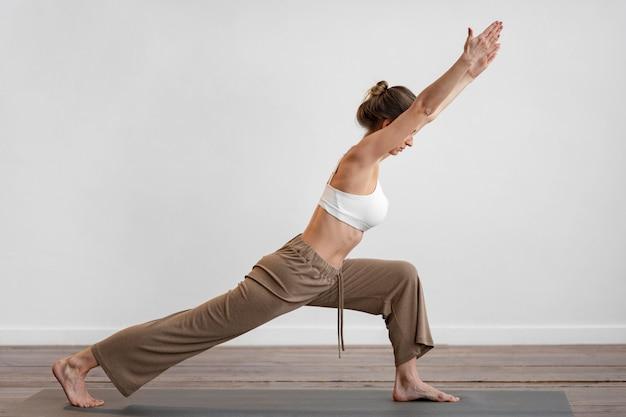 Zijaanzicht van vrouw thuis beoefenen van yoga met kopie ruimte Gratis Foto