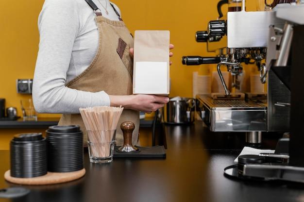 Zijaanzicht van vrouwelijke barista koffiebonen malen Gratis Foto