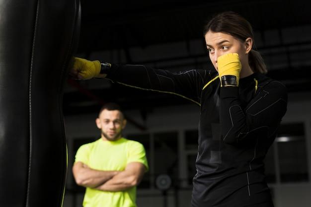 Zijaanzicht van vrouwelijke bokser met beschermende handschoenen die zware zak ponsen Gratis Foto
