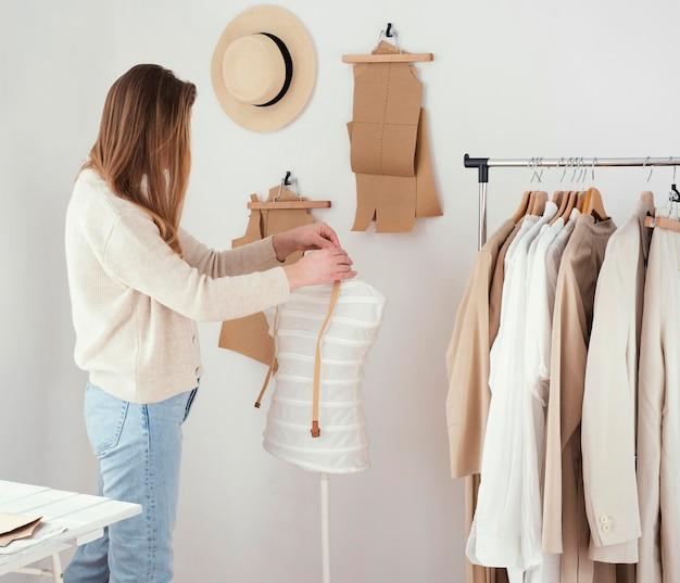 Zijaanzicht van vrouwelijke kleermaker in de studio met kleren Gratis Foto