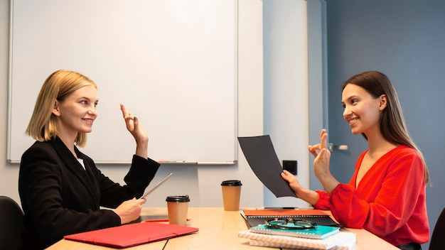 Zijaanzicht van vrouwelijke ondernemers die gebarentaal gebruiken Gratis Foto