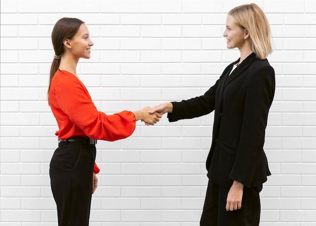 Zijaanzicht van vrouwen die elkaar groeten Gratis Foto