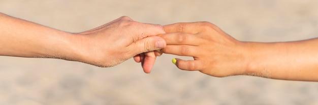 Zijaanzicht van vrouwen die handen op strand houden tijdens het trainen Gratis Foto