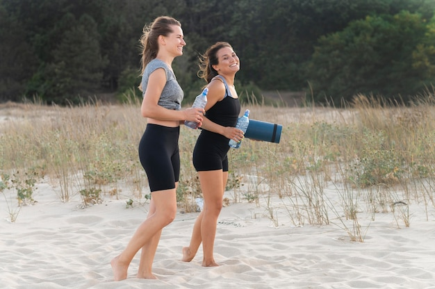 Zijaanzicht van vrouwen die met waterflessen op het strand uitoefenen Gratis Foto