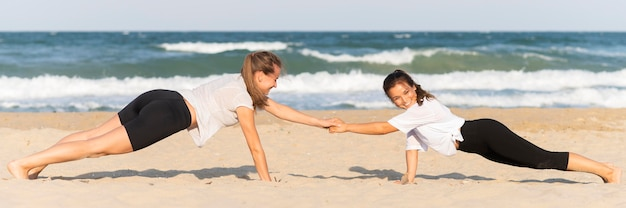 Zijaanzicht van vrouwen die push-ups op het strand doen Gratis Foto