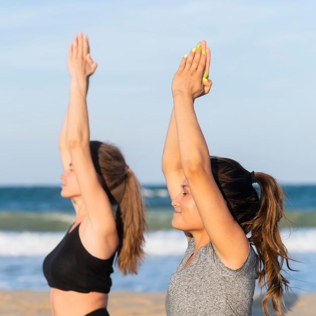 Zijaanzicht van vrouwen die samen yoga op het strand doen Gratis Foto