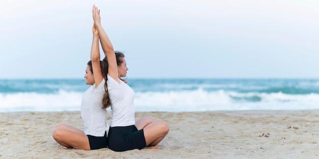 Zijaanzicht van vrouwen die yoga op het strand beoefenen Gratis Foto