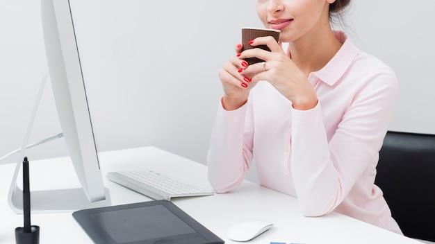 Zijaanzicht van werkende vrouw bij de kop van de bureauholding van koffie Gratis Foto