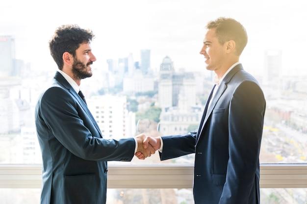 Zijaanzicht van zakenman die elkaar handen schudden Gratis Foto